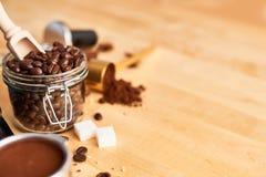 在玻璃瓶子和portafilter的新近地烤咖啡豆 库存照片