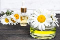 在玻璃瓶子特写镜头的春黄菊精油在与雏菊和一个瓶的一张桌上油 免版税库存图片