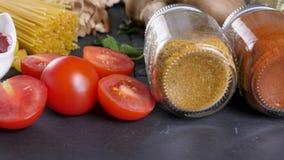 在玻璃瓶子的不同的香料在切的蕃茄和蕃茄souce旁边 影视素材