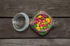 在玻璃瓶子的五颜六色的甜糖果在木背景 库存照片
