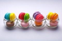 在玻璃瓶子的五颜六色的鲜美蛋白杏仁饼干在灰色背景 库存图片