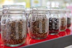在玻璃瓶子的咖啡豆在咖啡馆柜台 库存图片