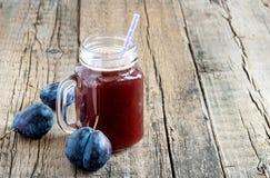 在玻璃瓶子的开胃菜新鲜的李子汁在木背景新李子圆滑的人拷贝空间 免版税库存照片