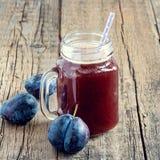 在玻璃瓶子的开胃菜新鲜的李子汁在木背景新李子圆滑的人正方形 库存图片