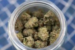在玻璃瓶子的消遣大麻在蓝色瓦片 免版税库存照片