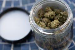 在玻璃瓶子的消遣大麻在蓝色瓦片 免版税库存图片