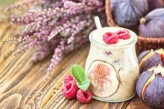 在玻璃瓶子的美好的健康开胃菜无花果果子圆滑的人奶昔装饰了新鲜的无花果桃红色莓顶视图 自然d 免版税库存图片