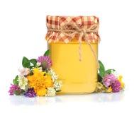 在玻璃瓶子的蜂蜜与花 库存照片