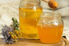 在玻璃瓶子的蜂蜜是在属性旁边 库存照片
