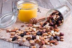 在玻璃瓶子的蜂蜜有在土气木背景的坚果的 免版税库存图片