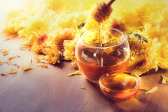 在玻璃瓶子的蜂蜜有蜂飞行和花的在一个木地板上 库存图片