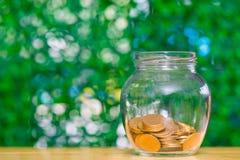 在玻璃瓶子的金币金钱在桌上在有绿色b的庭院里 免版税库存照片