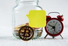 在玻璃瓶子的Bitcoins古铜色金黄硬币在白色木桌上 设置与一真正的欧元的cryptocurrencies,在瓶子的美元 免版税库存照片