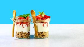 在玻璃瓶子,在玻璃的新鲜的莓果的两个草莓酸奶 草莓,在蓝色隔绝的奶油奶酪健康早餐 免版税图库摄影