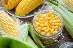 在玻璃瓶子,新鲜和煮熟的玉米的罐装甜玉米在玉米棒 免版税库存照片