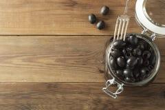 在玻璃瓶子,木背景的烂醉如泥的挖坑的黑橄榄 Mediteranian食物 r 免版税图库摄影
