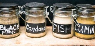 在玻璃瓶子,胡椒,豆蔻果实,鱼宴的,小茴香香料的五颜六色的香料 库存图片