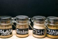 在玻璃瓶子,胡椒,豆蔻果实,鱼宴的,小茴香香料的五颜六色的香料 库存照片