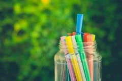在玻璃瓶的各种各样的颜色笔在水泥地板上有在葡萄酒样式的绿色灌木背景 免版税库存照片