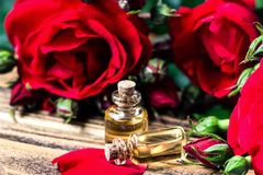 在玻璃瓶的精油有红色玫瑰的开花和在木背景的瓣 浴秀丽构成油用肥皂擦洗处理 温泉和芳香疗法concep 免版税库存图片