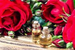 在玻璃瓶的精油有红色玫瑰的开花和在木背景的瓣 浴秀丽构成油用肥皂擦洗处理 温泉和芳香疗法concep 图库摄影