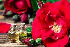 在玻璃瓶的精油有红色玫瑰的开花和在木背景的瓣 浴秀丽构成油用肥皂擦洗处理 温泉和芳香疗法concep 免版税图库摄影