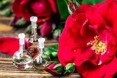 在玻璃瓶的精油有红色玫瑰的开花和在木背景的瓣 浴秀丽构成油用肥皂擦洗处理 温泉和芳香疗法concep 库存照片