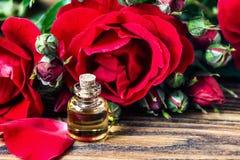 在玻璃瓶的精油有红色玫瑰的开花和在木背景的瓣 浴秀丽构成油用肥皂擦洗处理 温泉和芳香疗法concep 免版税库存照片