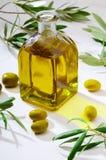 在玻璃瓶的额外处女橄榄油 前景 包括叶子和橄榄树枝 库存照片