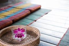 在玻璃的兰花花 在席子的泰国后面架靠背枕头 泰国sc 库存照片