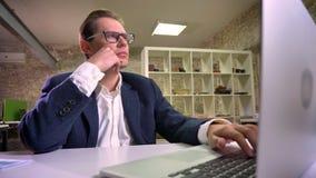 在玻璃的凉快的白种人工作的男性和衣服集中于输入他的膝上型计算机和坐在单独办公室 股票录像