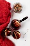 在玻璃的加香料的热葡萄酒用桔子和香料在红色毛线衣附近 免版税库存图片