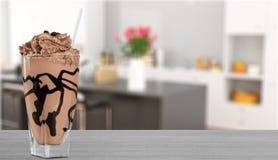 在玻璃的可口巧克力奶昔在桌上 免版税库存照片