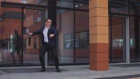在玻璃的年轻可爱的商人在商业中心附近在他的手上的跳舞拿着一个公文包 慢 影视素材
