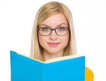 在玻璃的愉快的学员女孩阅读书 免版税库存图片