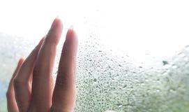 在玻璃的手指与水滴 递有使模糊的少妇在窗口 雨水滴在玻璃背景的 有选择性 免版税库存照片