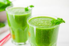在玻璃的新鲜的绿色菠菜圆滑的人在白色木背景 概念健康生活方式 选择聚焦 背后照明 复制 免版税库存照片