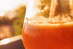 在玻璃的橙色圆滑的人与在日落的秸杆 图库摄影