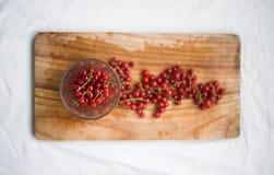 在玻璃的红浆果在木背景 在视图之上 免版税图库摄影