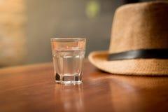 在玻璃的纯净的水与葡萄酒帽子 免版税库存照片