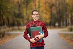 在玻璃的组长与文件夹在秋天公园之前去 免版税库存图片