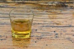 在玻璃的老,好李子白兰地酒在难看的东西木桌上 库存照片