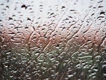 在玻璃的背景雨珠 库存图片