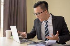 在玻璃的英俊的被注重的年轻亚洲商人愤怒与膝上型计算机 免版税库存照片