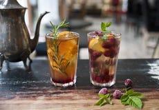 在玻璃的茶在以咖啡馆和葡萄酒茶壶为背景的老桌上 佐井用桔子和迷迭香和茶与 库存照片