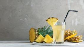 在玻璃的菠萝新鲜的汁在一张木桌上 图库摄影