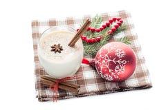 在玻璃的蛋黄乳鸡尾酒安排了与圣诞节装饰isol 库存照片