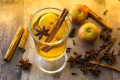 在玻璃的被仔细考虑的萍果汁在木桌上 圣诞节饮料 免版税库存照片