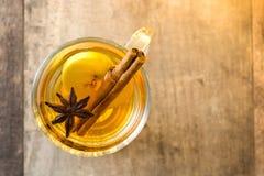 在玻璃的被仔细考虑的萍果汁在木桌上 圣诞节饮料 免版税库存图片