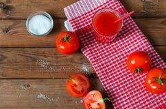 在玻璃的西红柿汁用新鲜的蕃茄和盐 背景土气木 库存图片